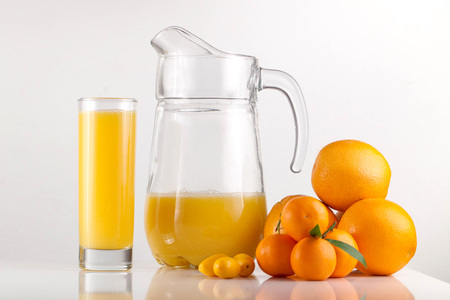 Orange juice in glass with composition of oranges on white background