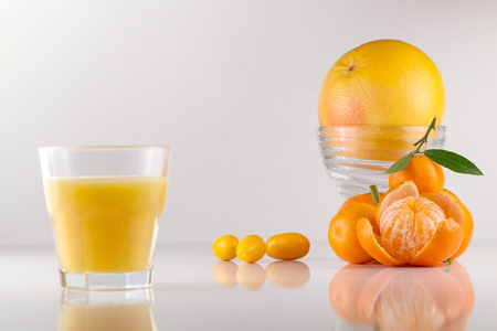 Peeled mandarine placed on a white surface together with orange and orange juice in glass Stock Photo