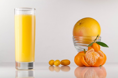 Close-up of orange juice glass next to the composition of oranges and peeled tangerine Stock Photo