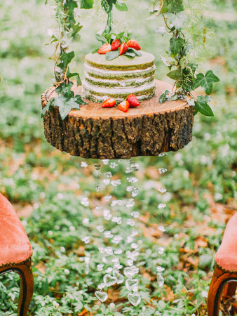 The composition of the green and white sponge cake with strawberries and placed on the stump decorated with pendent glass hearts in the forest