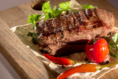 Tasty, juicy, big steak placed on a pita bread with grilled vegetables and herbs. Composition on a wooden board.