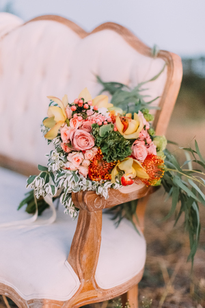 velvet dress: The colourful bouquet consisted of the pink and yellow roses are placed on the wooden knob of the white stylish sofa