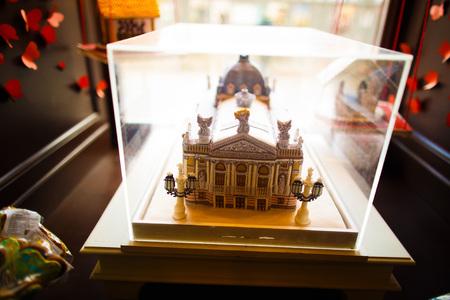 De close-upfoto van het chocolade gemaakte huis dat onder het glas op de vensterbank wordt geplaatst