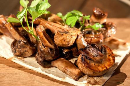 button: Cooking mushrooms on the grill in the restaurant Stock Photo
