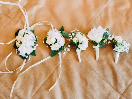 The above view of the wedding mini-bouquets and flower armlet wrapped in white ribbons placed on the bed