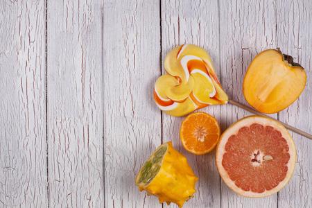 Gesneden fruit en zoete gekleurde snoepjes op een witte houten plank