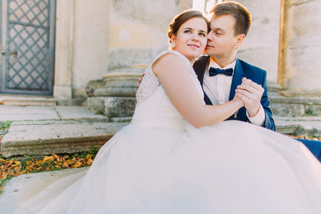 marrying: Romantic close-up portrait of the newlyweds sitting on the stairs. The groom is kissing bride in the cheek.