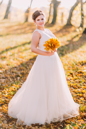 The full-length view of the smiling bride holding the bouquet of the yellowed leaves.