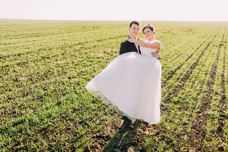 trash the dress: The full-length view of the groom carrying the bride at the background of the field.