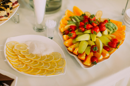 The above view of the fruit composition consisted of strawberries, apples, oranges, lemons placed on the wedding table