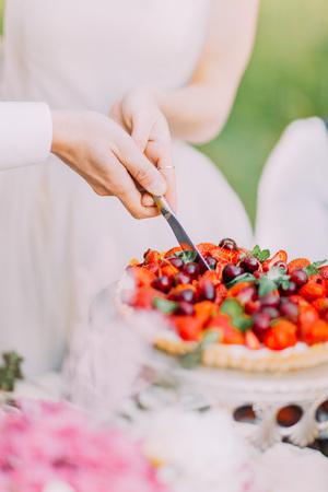 ナイフを持って木に晴れた日の間にチェリーとイチゴのウェディング ケーキの最初の部分を切削新婚者の手のクローズ アップ写真 写真素材