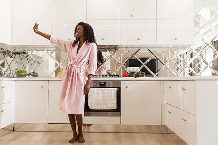 Attractive femme noire heureuse debout dans la cuisine et faisant de la selfie. Femme vêtue d'un peignoir rose et a de longs cheveux bouclés.