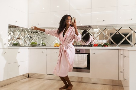 Happy young black woman wearing bathrobe dansing in the kitchen with the phone in her hands. Stockfoto