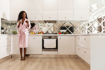 Attractive black girl standing in the kitchen with the phone and glass of water in her hands. Woman wearing pink bathrobe and has long dark curly hair.