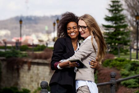 Black businesswoman hugging white woman. Women standing in the park.