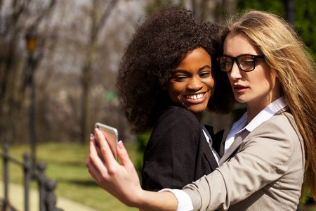 Attractive black woman and white woman doing selfie in the park. Women wearing suits. Stock Photo