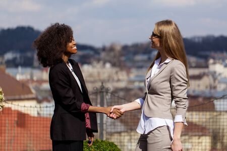 Two happy businesswomen shaking hands with each other. one woman is black. Stock Photo