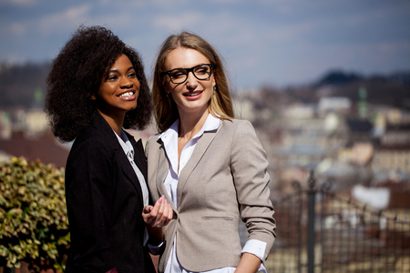 smiled: Smiled businesswomen in suits posing for camera in the park with great city view. Black woman has curly hair.