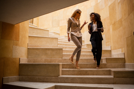 Two attractive businesswoman going downstairs. Women wearing suits. One woman is black.