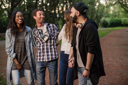 spolužák: Group of friends walking in the park and talking.