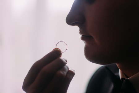 suspicion: Young handsome groom looking on wedding ring in his hand