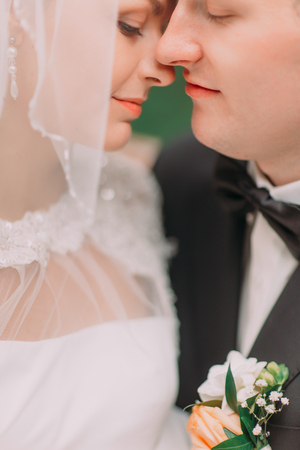 aged: The newlyweds are touching noses. The side close-up portrait.