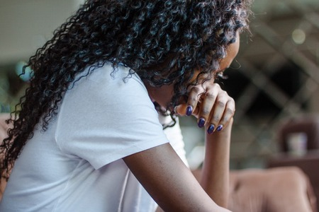 Black attractive woman sitting on the couch and crying. Foto de archivo