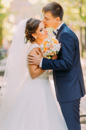 back alley: The romantic portrait of the happy newlyweds. The groom is kissing the bride on the head in the park.