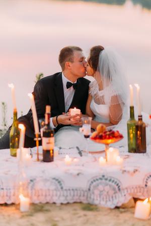 Het zittende pasgetrouwde stel kussen zich achter de picknickset versierd met glanzende kaarsen in flessen. Stockfoto