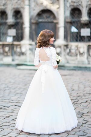 The back view of the bride with the wedding bouquet in the street.