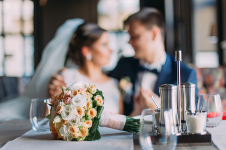 Romantic moment of newlywed couple. Stylish young groom and his beautiful bride holding each other. Wedding bouquet laying on served table at foreground