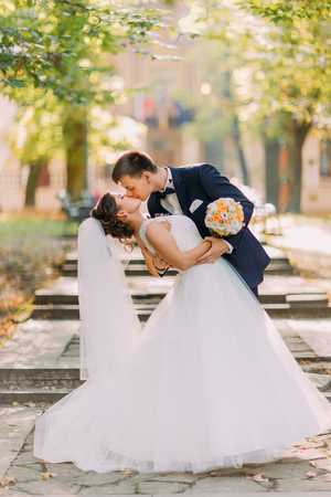The full-length view of the kissing newlyweds at the background of the park.