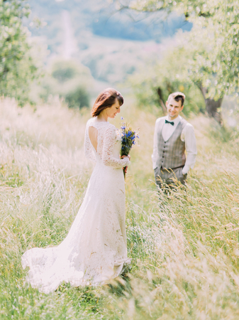 weddingrings: The full-length back view of the bride holding the blue flowers at the blurred background of the smiling groom.