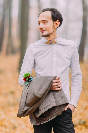 Portrait of stylish hipster groom in white shirt and bow tie. Autumn forest
