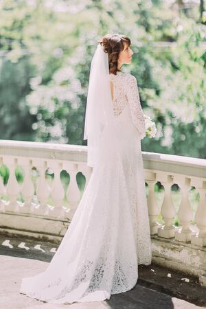 The back view of the bride standing on the balcony. Stock Photo