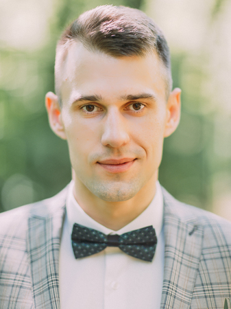 The close-up portrait of the groom with black bow-tie in the park.