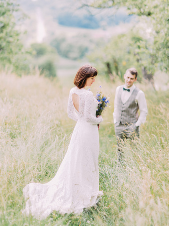 weddingrings: The back view of the bride with the blue flowers at the blurred background of the groom in the field.