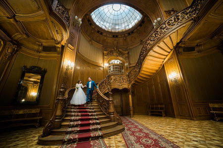 Cheerful newlywed couple is groing down the ancient stairs. Horizontal view. Stock Photo