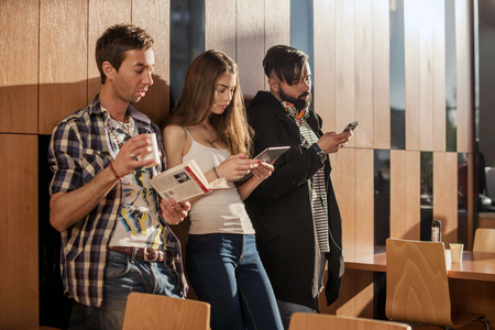 rumour: Three young people standing in the room near the wall with gadgets in their hands.