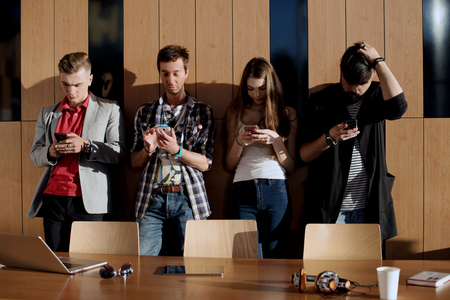 rumour: Four young people standing in the room near the wooden wall and look at the screens of their phones. Stock Photo
