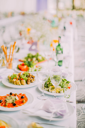 Different types of dishes placed on the wedding table set.