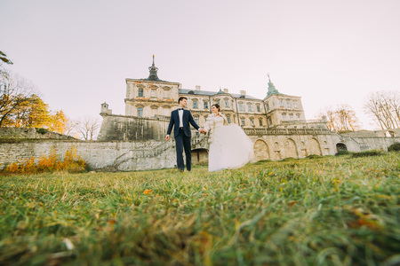 The full-length view of the newlyweds holding hands and walking in the yard of the castle. Down view Stock Photo