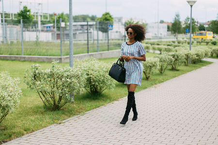 stylishly: The walk of the stylishly dressed afro-american along the street.