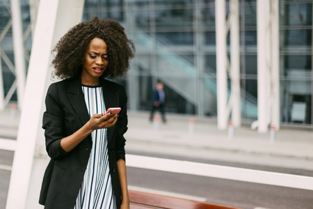 Upset afro-american woman is looking at the mobile phone. Close-up portrait.