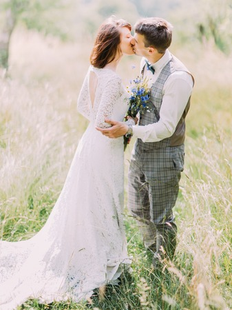 The side full-length portrait of the kissing newlyweds with the blue bouquet in the field.
