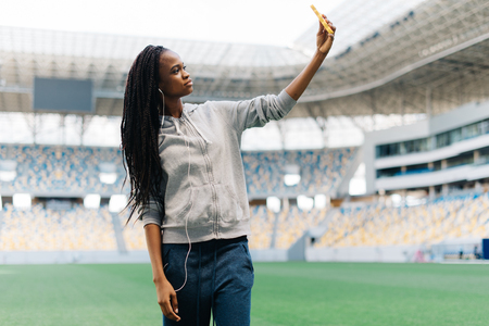The beauitful thoughtful afro-american teenager is taking selfie via the mobile phone on the stadium.