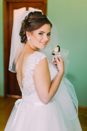 Gorgeous bride in white dress posing, holding cute little boutenniere and looking over her shoulder