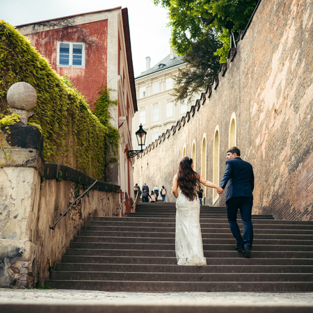 The magnificent newlyweds are going up the old baroque stairs. Prague location. The close-up back view.