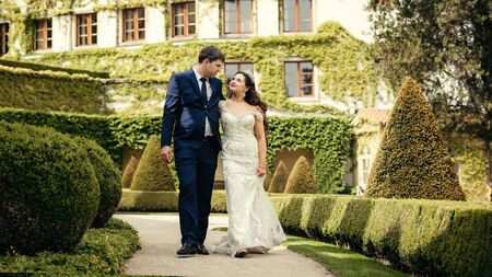 The walk of the cheerful hugging newlyweds along the magnificent garden in Prague.