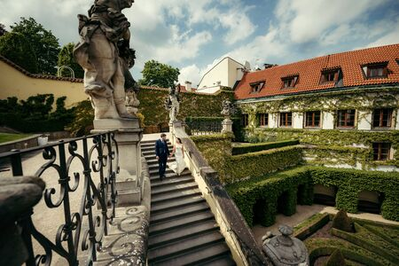 The beautiful newlyweds are going down the stairs in the magnificent garden decorated with sculptures. Prague location.